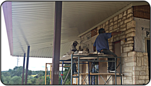 Masons install rock on the ranch house.