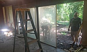Workers remove dated sliding glass doors