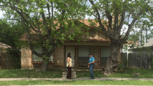 Two people in front of a house.
