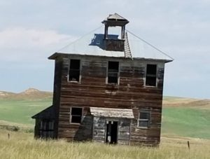 A falling down house in the middle of a field.