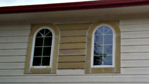 Unpainted siding around arch windows.