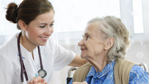 Nurse and elderly woman smiling at each other