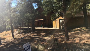 Sun shining on a mountain cabin in Ruidoso, NM